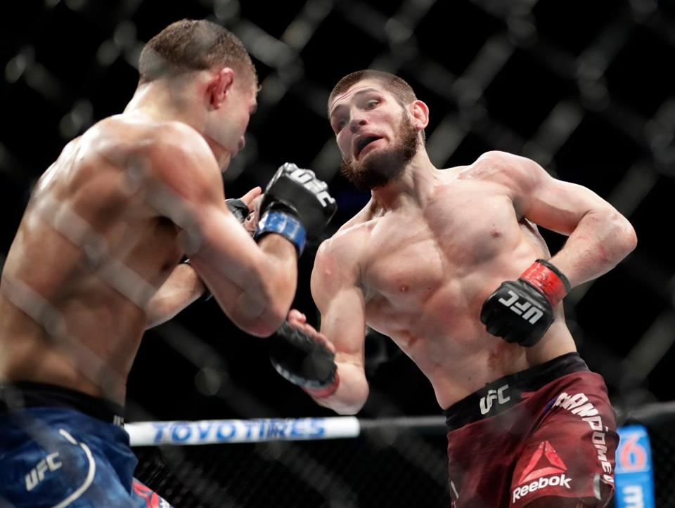 Al Iaquinta, left, deflects a punch from Russia's Khabib Nurmagomedov during the fifth round of a lightweight title bout at UFC 223 early Sunday, April 8, 2018, in New York. Nurmagomedov won the fight. (AP Photo/Frank Franklin II)