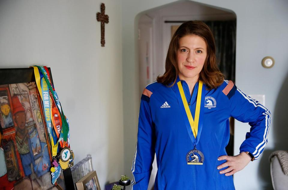 Brighton, MA -- 4/08/2018 - Christine Yost, 35, of Brighton poses for a portrait with her Boston Marathon medal at her apartment in Brighton. (Jessica Rinaldi/Globe Staff) Topic: Marathon Reporter: