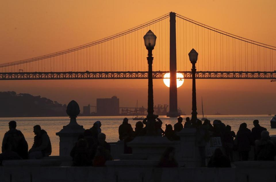 Tour operator Off the Grid asks travelers to not use smartphones on trips. The company will make its first trip to Lisbon in July. People in Lisbon's Comercio Square watch the sun set behind the April 25th Bridge.