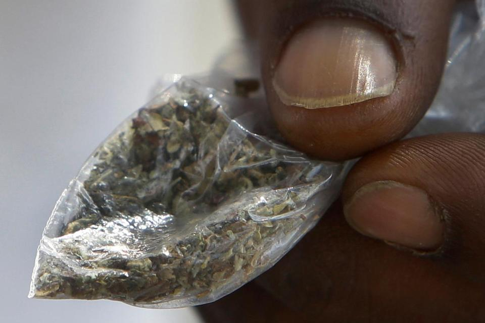 A man holds a bag of synthetic marijuana.