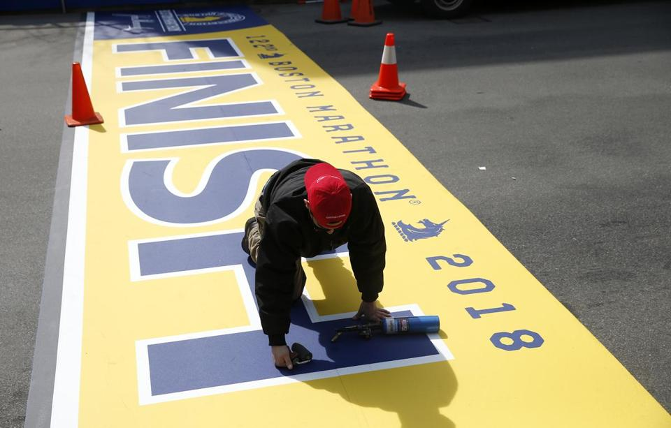 Jonathan Rodriguez of Peabody worked to lay down the Finish Line for the 2018 Boston Marathon on Boylston Street on Thursday.