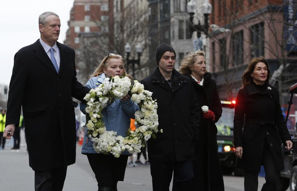 Governor Charlie Baker (left) escorted Patricia Campbell, the mother of Krystle Campbell, as she carried a wreath Sunday in honor of her late daughter and the others killed in the Boston Marathon bombings five years ago.