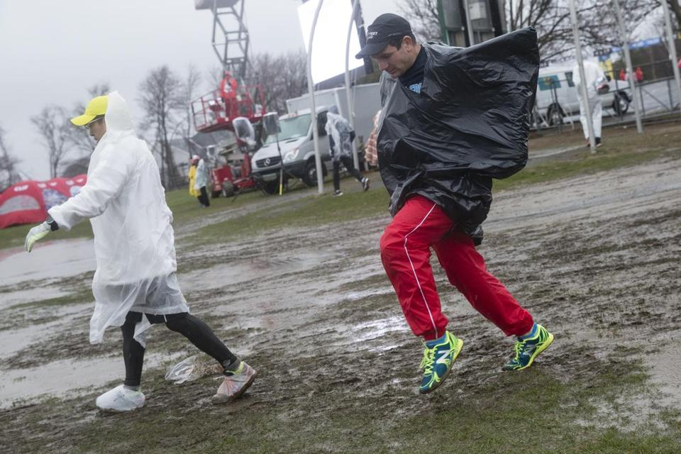 Runners make their way through the rain and mud in the athlete's village prior to the start of the Boston Marathon Monday.