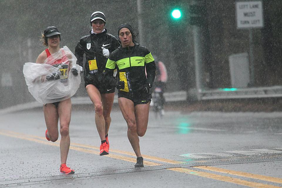 Flanagan (center) trails women's winner Desiree Linden (right) by a couple of steps during a downpour in Wellesley.