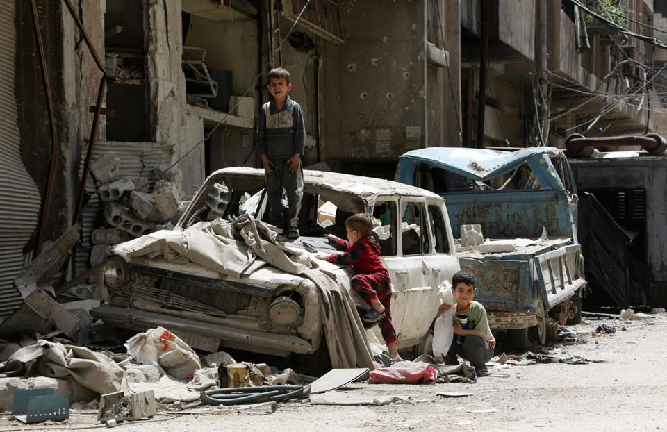 Syrian boys play on a destroyed car in the former rebel-held Syrian town of Douma on the outskirts of Damascus on April 19, 2018, five days after the Syrian army declared that all anti-regime forces have left Eastern Ghouta, following a blistering two month offensive on the rebel enclave. The regime in February launched a blistering assault on Eastern Ghouta, a semi-rural area within mortar range of central Damascus that had been in opposition hands for six years. / AFP PHOTO / STRINGERSTRINGER/AFP/Getty Images