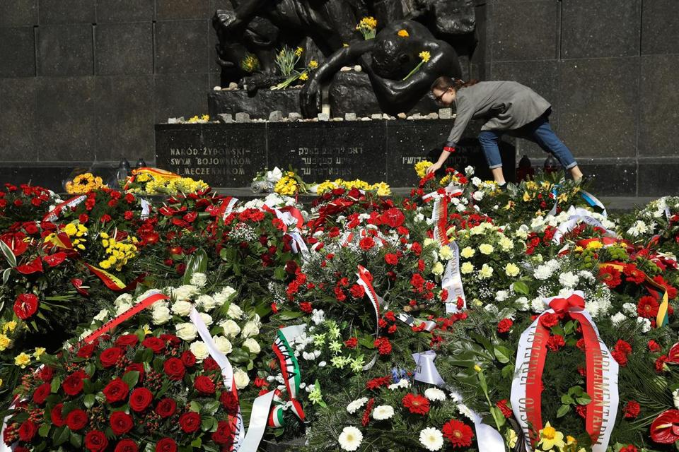 A woman placed daffodils at the Ghetto Heroes Monument after a ceremony marking the Warsaw Ghetto Uprising.