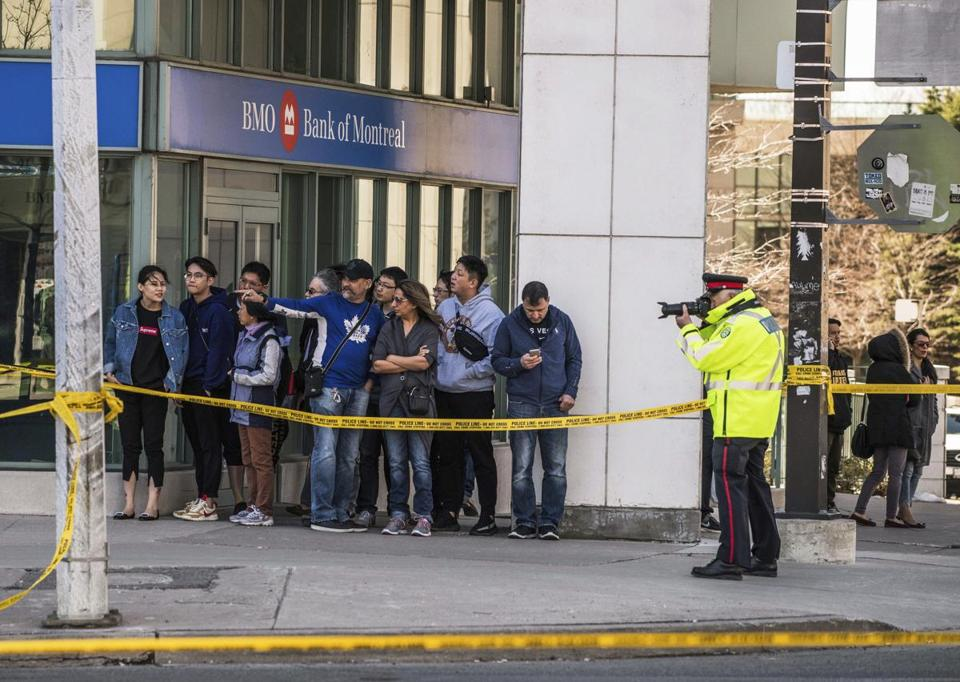 A police officer took pictures of the scene as emergency services closed Yonge Street.
