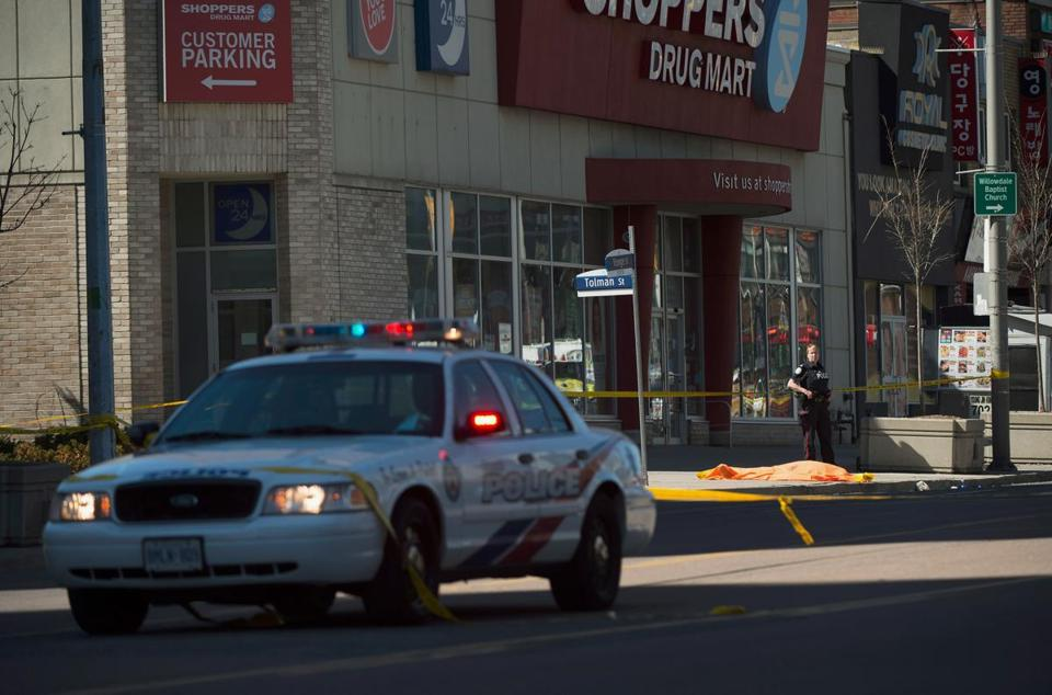 A police officer stood near a covered body near a store.
