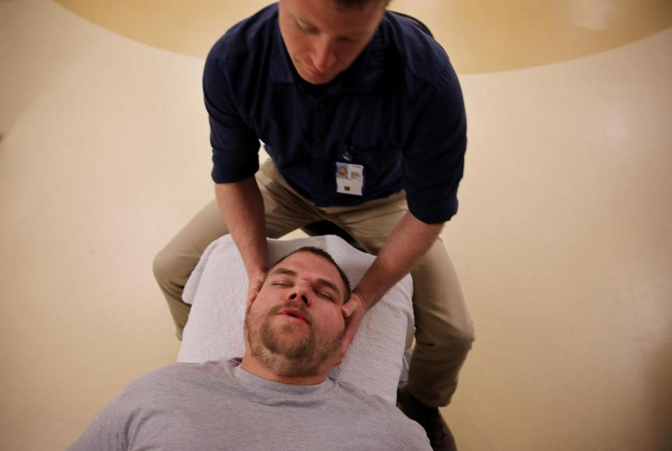 Chiropractor Derek Golley, seated, works with Army Veteran Stephen Wilber at the White River Junction VA Medical Center. Wilber is being treated for neck and lower back pain.