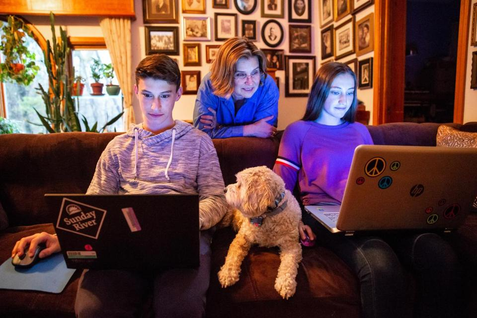 "Noula Thibault watches as her children, Charlie and Lydia, play a game of ""Fortnite"" together on the couch."