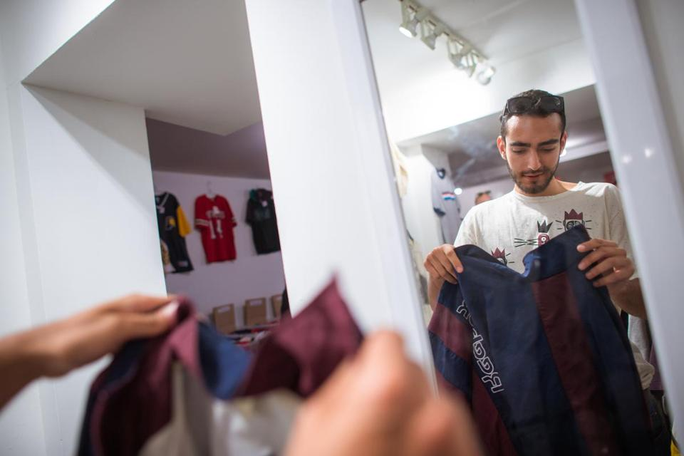 Dudi Luski, of Israel, checks out a Reebok jacket being sold on consignment in Jeff Casler's new store, Thrive Market on Newbury St., in Boston, Friday, April 27, 3018. Casler is having his third time around. The former CEO of the Second Time Around consignment chain grew the business into a national brand before selling it to private equity firm several years ago. Last year, he watched from the outside as the company imploded after years of mismanagement, leaving thousands of consigners enraged and left in the lurch. Photo by Gretchen Ertl for The Boston Globe