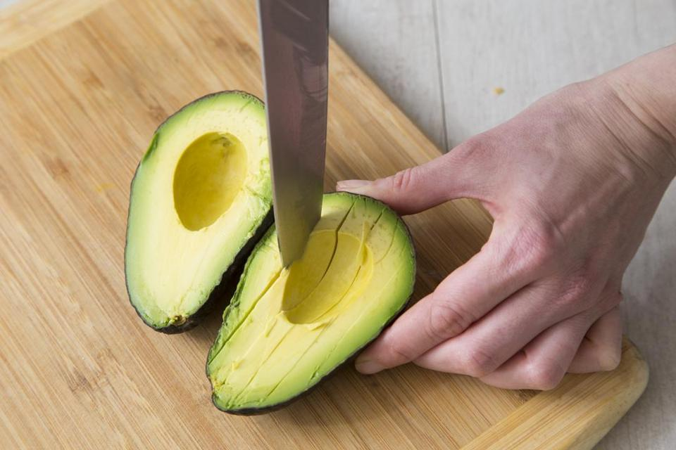 There's no need to skin an avocado half to remove the flesh. Using a paring knife, cut through the soft flesh down to, but not through, the skin, in a crosshatch pattern to create cubes or slices. Then use a soup spoon to scoop out the pieces.
