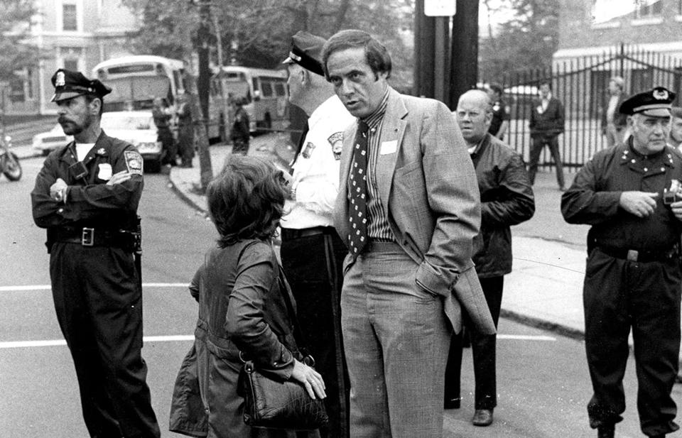 Boston Police Commissioner Robert di Grazia talks with a woman outside of South Boston High School about problems in the neighborhood surrounding the federal court-ordered integration of the city's schools on Sep. 20, 1974.