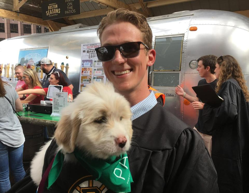 Northeastern Graduate Jake Heney Holds A Puppy At The Opening Ceremonies  For The Patios On Boston