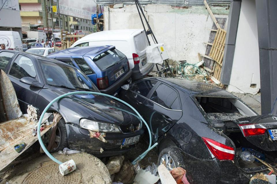 Damaged Vehicles Are Pushed Against A Wall After Being Washed Away During Flooding In District