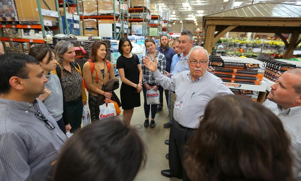 Sinegal, second from right, leads students from the Sloan School class through the Waltham Costco store.