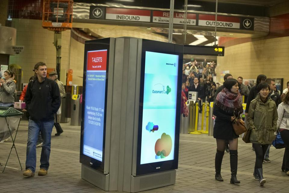 Commuters walked past a digital advertising and information screen at the Harvard Square MBTA station.