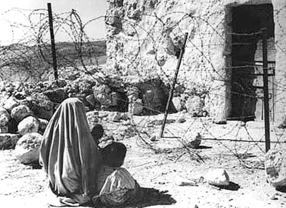 "A Palestinian refugee and her child separated from their home by the ""green line"" after the 1948 war."