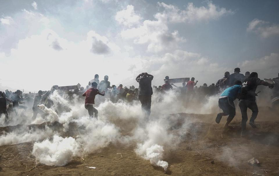 Palestinian protesters ran for cover from Israeli tear gas during clashes near the border with Israel in the east of Gaza City on Friday.