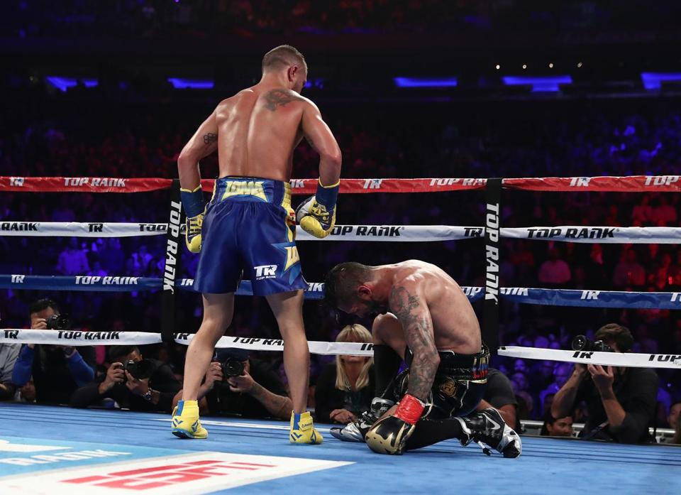 Vasiliy Lomachenko (left) stands over Jorge Linares after knocking him down in the tenth round.