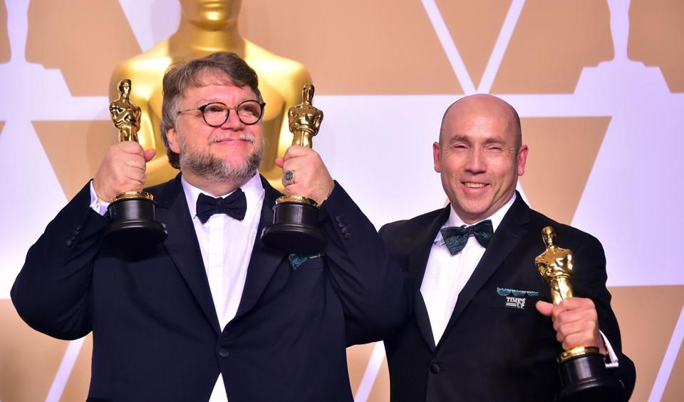 "Director Guillermo Del Toro (left), with producer J. Miles Dale, poses with Oscars for best director and best picture for the film ""The Shape of Water."""