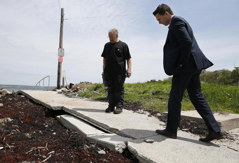 Nahant selectman Enzo Barile (left) and state Senator Brendan Crighton toured the coastline last week. They looked at a sidewalk near Short Beach that was damaged by winter storms.