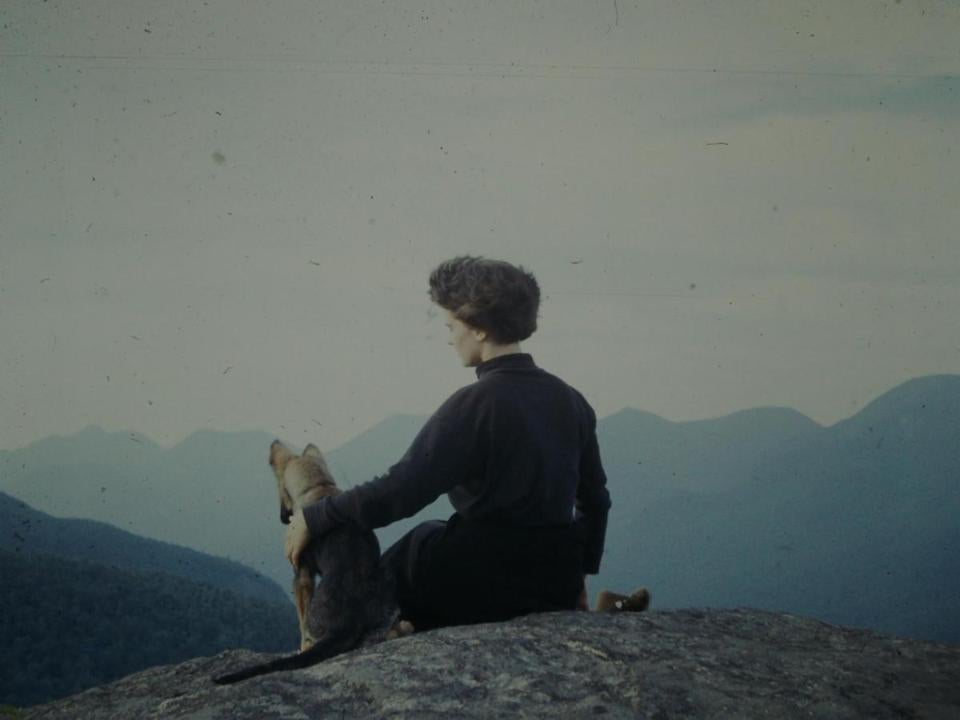 During a hike along the Three Brothers peaks in Keene Valley, N.H., in 1959, the year she married, Mrs. Lange sits with Hans, the Langes' German shepherd puppy.