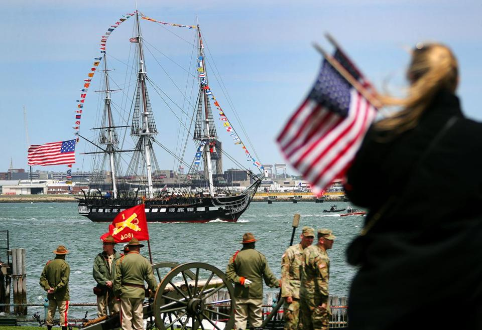 People stood on Castle Island with flags as the USS Constitution was saluted by the Concord Independent Battery (rear) and the 101st Field Artillery that fired in a return salute.