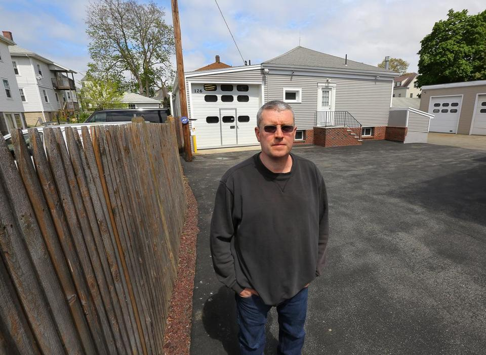 Quincy, MA - 5/13/18 - Bill Haugh (cq) is fighting a proposed housing project near his home, on Old Colony Avenue in Quincy. He claims removal of the two white buildings at left and a one-story brick building and garage (at left, out of frame) will cause flooding in front of his home (center rear). Photo by Pat Greenhouse/Globe Staff Topic: sowollaston Reporter: Jill Terreri Ramos