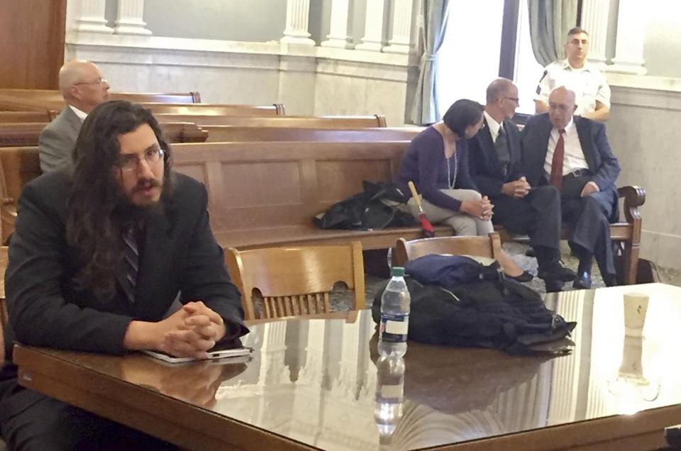 Michael Rotondo, left, sits during an eviction proceeding in Syracuse, N.Y., brought by his parents, Mark and Christina, of Camillus. The two parents confer with their lawyer, Anthony Adorante, in the court gallery behind. Rotondo told the judge Tuesday, May 22, 2018, he knows his parents want him out of their Camillus home, near Syracuse. But he argued he's entitled to six months more time. (Douglass Dowty /The Syracuse Newspapers via AP)