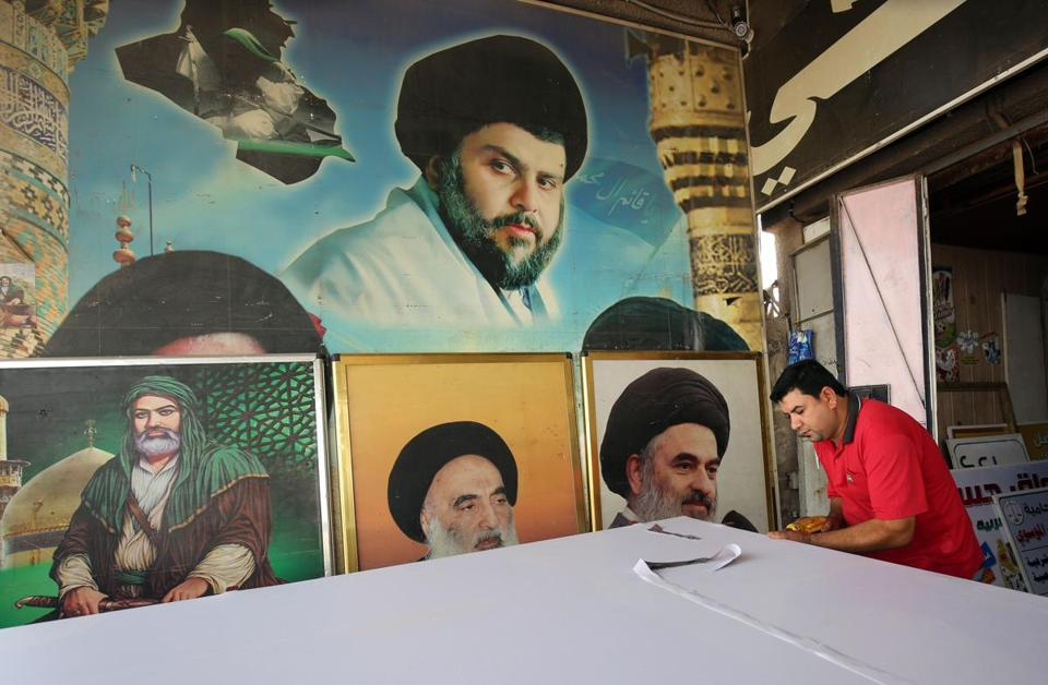 An Iraqi labourer works on a poster of Shiite cleric Moqtada Sadr at a printing shop in Sadr City, east of the Iraqi capital Baghdad on May 23, 2018. - Sadr -- whose fighters were once accused of sectarian killings -- has reinvented himself as an anti-graft crusader looking to bridge Iraqi society in alliance with secular leftists. (Photo by AHMAD AL-RUBAYE / AFP) (Photo credit should read AHMAD AL-RUBAYE/AFP/Getty Images)