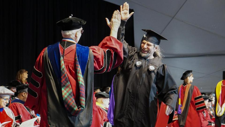 David D'Antonio of Arlington high-fives with dean of undergraduate studies Arthur Heinricher upon receiving his diploma from Worcester Polytechnic Institute.