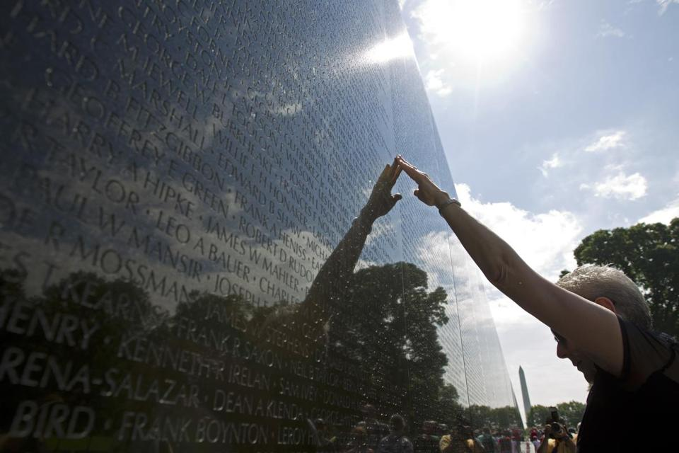 Sara Songy touches her friend's name at Vietnam Veterans Memorial wall, ahead of Memorial Day on Sunday, May 27, 2018, in Washington. (AP Photo/Jose Luis Magana)