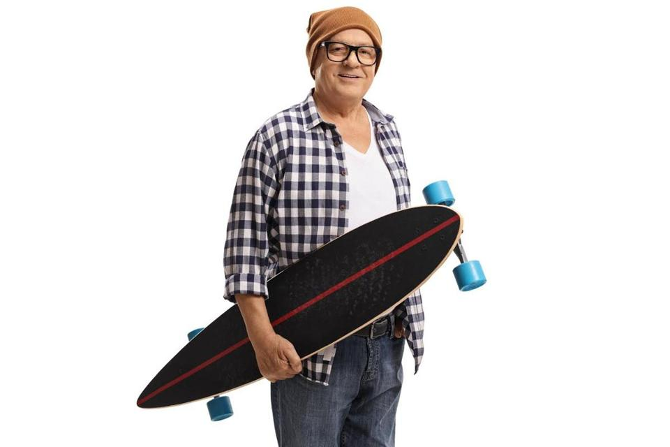 Old hipster holding a longboard isolated on white background