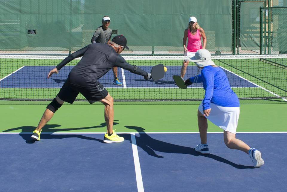"In pickleball, players can't volley the ball when in the ""kitchen"" (the green area)."