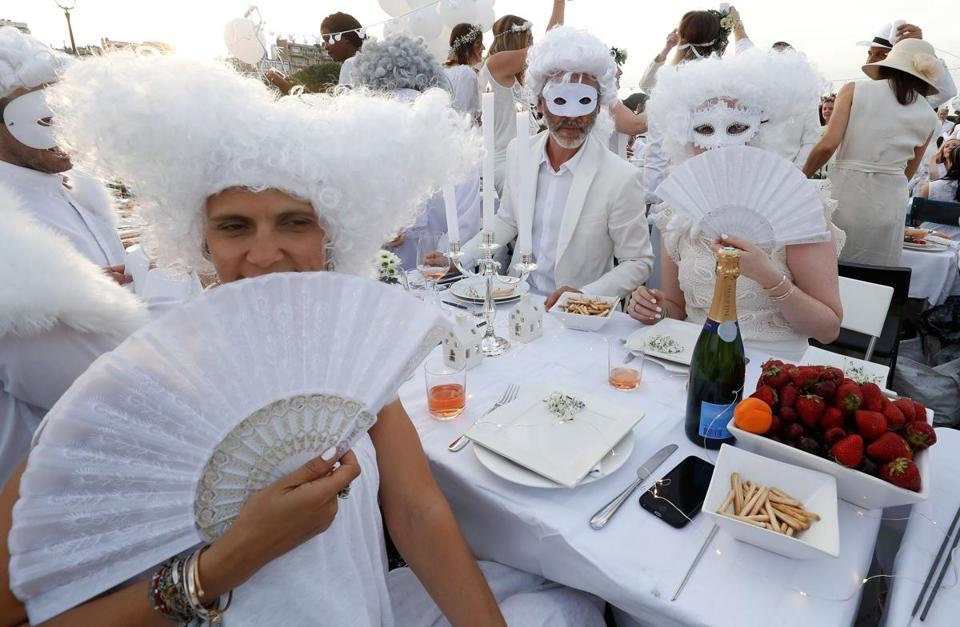"People dressed in white share a diner during the 30th edition of the ""Diner en Blanc"" (Dinner in White) event on the Invalides esplanade in Paris on June 3, 2018 with the Grand Palais in background. The ""Diner en Blanc"" is a chic secret pop-up style picnic phenomenon originally started in France. / AFP PHOTO / FRANCOIS GUILLOTFRANCOIS GUILLOT/AFP/Getty Images"