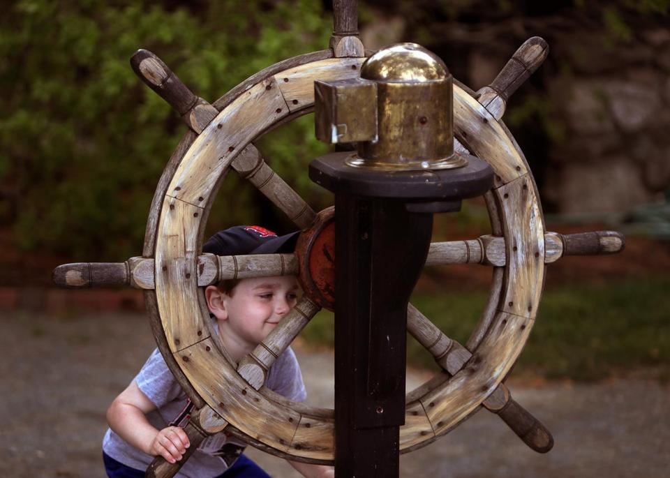 Salem, MA - 6/02/2018 - 3 year old Theodore Hoffman, of Salem plays with a ships wheel display on the grounds of the museum. The House of Seven Gables is celebrating its 350th anniversary. - (Barry Chin/Globe Staff), Section: Regional/All Zones, Reporter: James Sullivan, Topic: 24zogables, LOID: 8.4.2123146174.