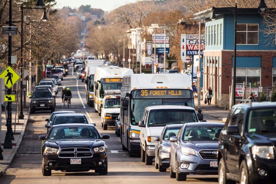 City buses in late 2017 sat in standstill traffic heading inbound on Washington Street in Roslindale near Forest Hills Station.