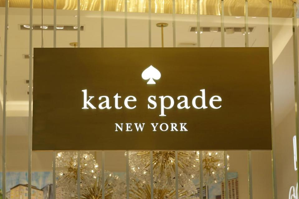A Kate Spade sign hangs in the window of a New York store.