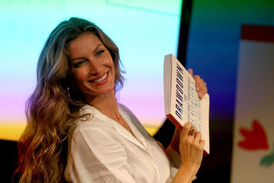 "Gisele Bundchen with a copy of ""Drawdown,"" a book on reversing global warming."