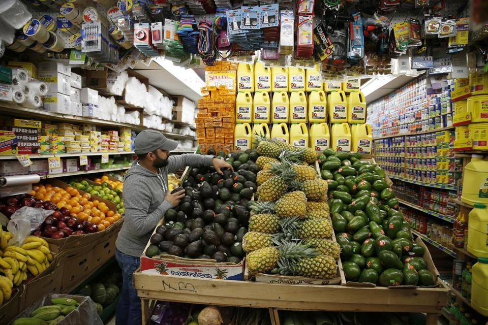 Lawrence, MA--6/6/2018-- A customer reaches for avocados inside Mellos Supermarket where a local hospital is funding healthy food options at local bodegas as part of a public health initiative. (Jessica Rinaldi/Globe Staff) Topic: 07bodega Reporter: