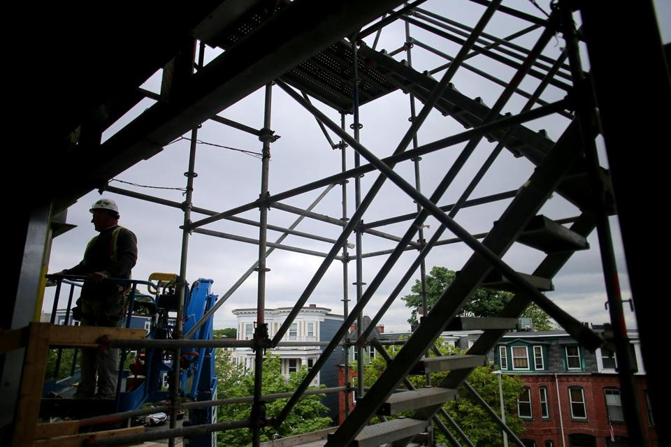 Scaffolding framed a worker outside Boston Collegiate Charter School, which is expanding its Dorchester site.