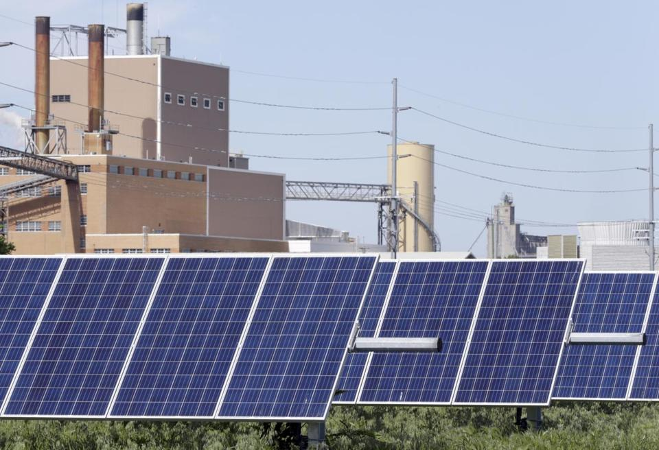 In this May 31, 2018, photo, a solar panel array collects sun light with the Fremont, Neb., with a power plant seen behind it. Solar energy is gaining traction in a small but growing number of Nebraska cities, but the technology still faces a number of obstacles that is keeping it from spreading faster. (AP Photo/Nati Harnik)