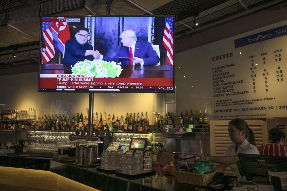 A screen at a restaurant in Singapore displayed a news broadcast of President Trump and North Korean leader Kim Jong Un.