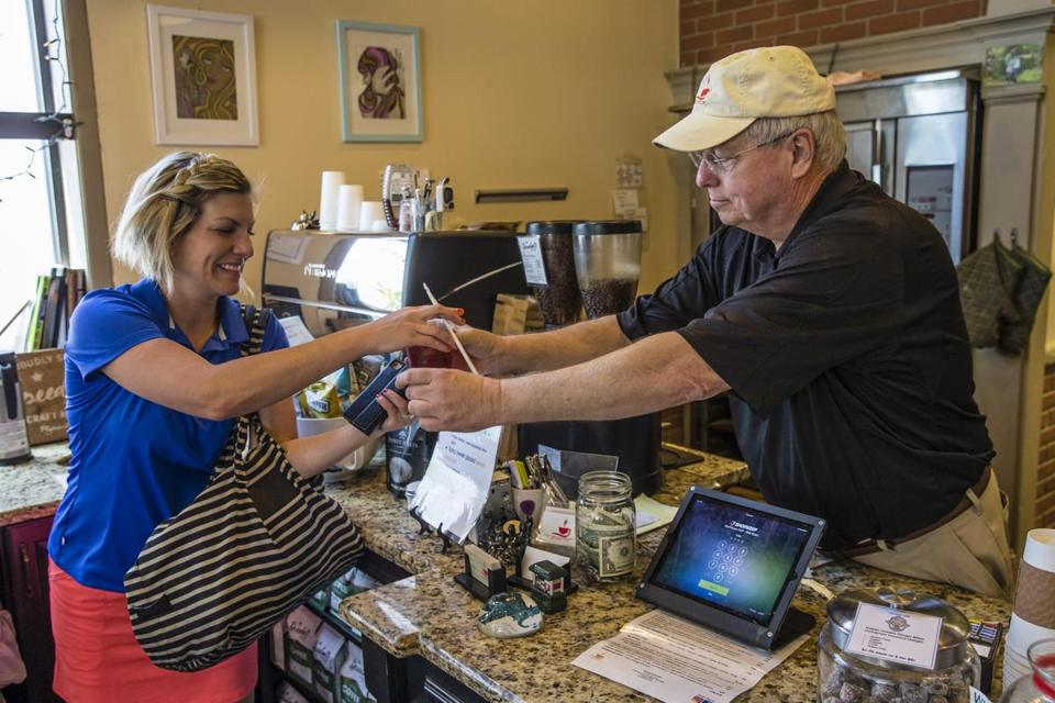 Justin O'Connor handed a customer an iced coffee as he worked in the Fuller Cup coffee shop in Winchester.