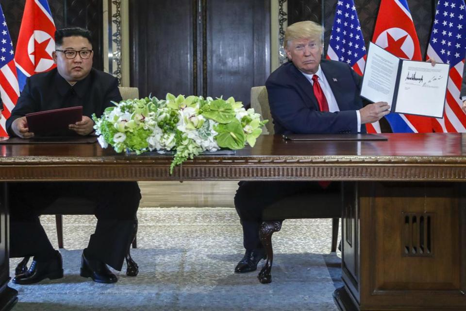 President Donald Trump helds up the document that he and North Korea leader Kim Jong Un just signed at the Capella resort on Sentosa Island on Tuesday.