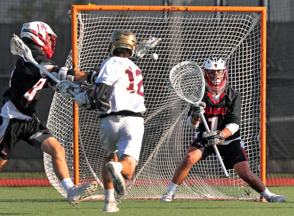 Boston, MA: 6-12-18: BC High's Christian Price (12) fires a first quarter shot by Wellesley goalie Teddy Darcey to give the Eagles a 3-0 lead. Wellesley's Jared Diamond is at far left. Wellesley visited Boston College High School for a Division One South boy's lacrosse semi-final match. (Jim Davis/Globe Staff)