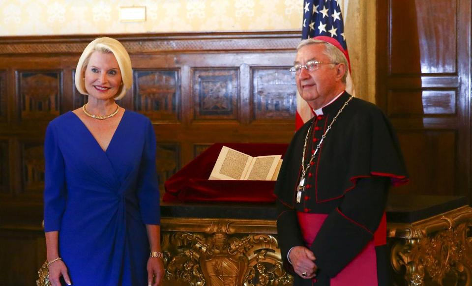 US ambassador to the Holy See Callista Gingrich (left) and Archibishop Jean-Luis Brugues posed in front of a copy of a letter written by Christopher Columbus that had been stolen from Vatican archives and returned by the United States.