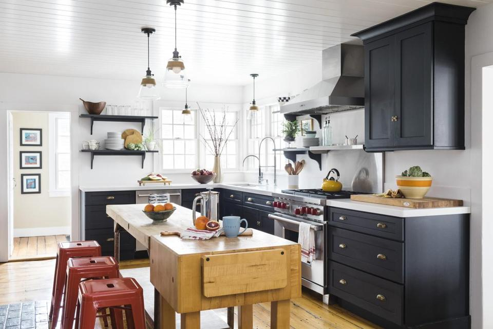 New black cabinets with thick white Corian countertops make a crisp, clean contrast with the worn wood kitchen floor and vintage butcher block island.