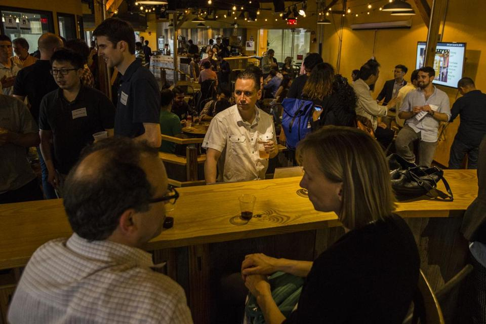 "Guests chatted during a weekly ""drinkup"" at the Venture Café in Cambridge's Kendall Square."